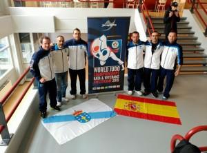 Los judokas de A.D. Judo Ferrolterra, con Alberto Castro - entrenador - y Pedro Alonso, posando con las banderas gallega y española y el cartel del mundial de Veteranos 2015